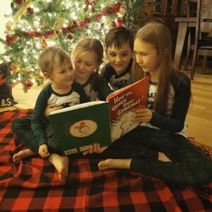 four kids reading next to a christmas tree